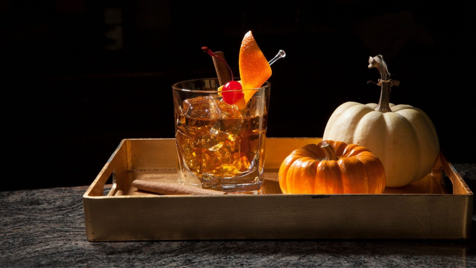 Fall tray with a glass of whiskey and pumpkins