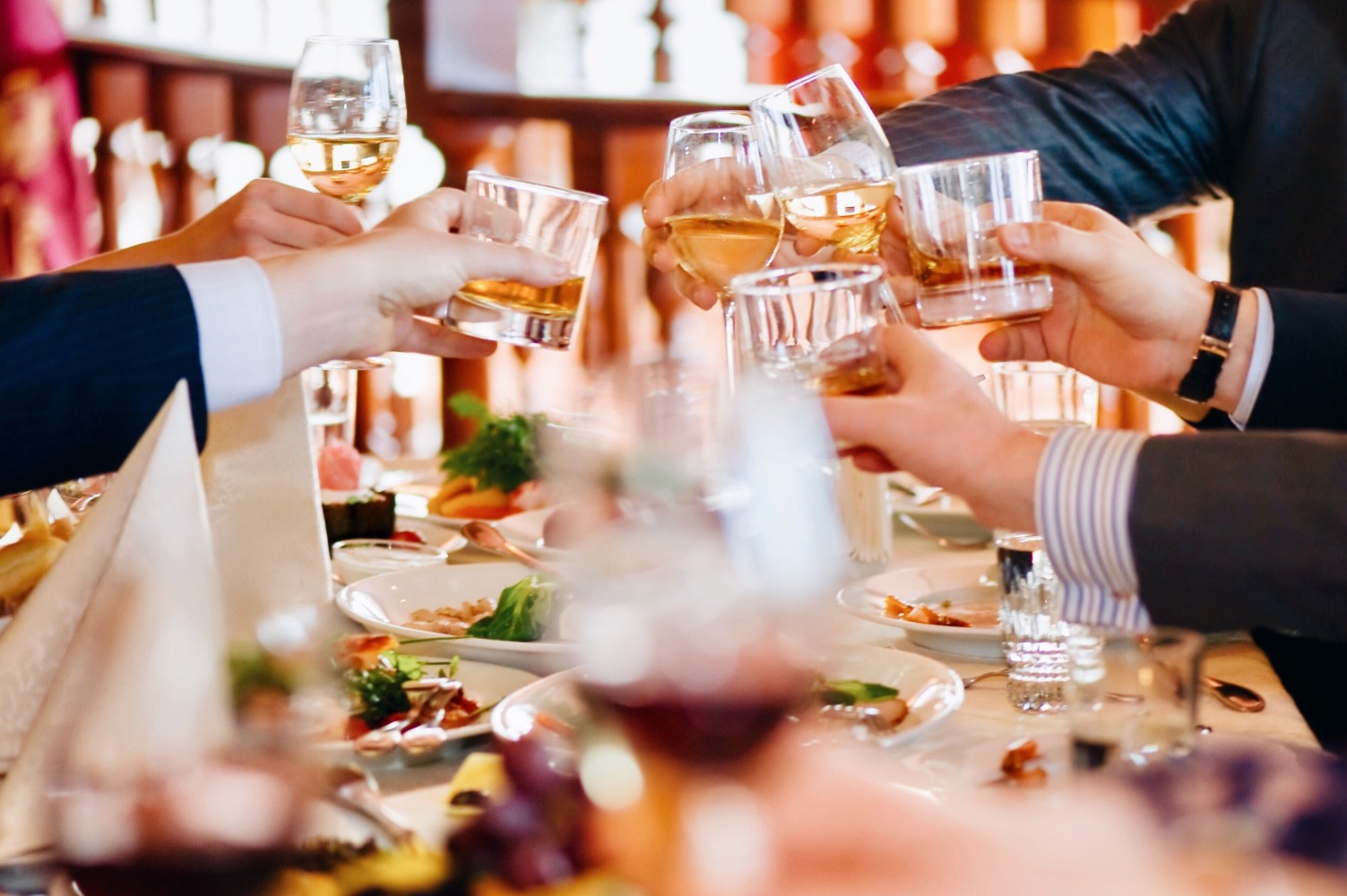 Guests at a wedding reception raising their glasses of whiskey and wine in cheers over a table with food